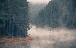 Man and dog on a boat in a mystic foggy lake near the forest. Fisherman and dog in big lake. A misty morning by the lake. Small fishing boat at the lake. Space for text