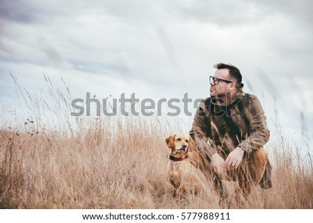 Man and dog resting in grassland