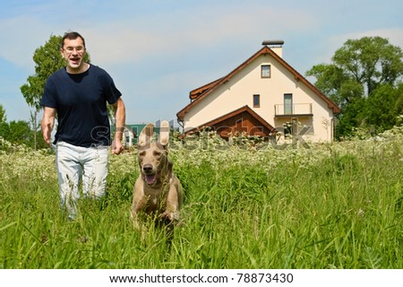 Man and dog running outdoors - stock photo
