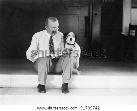 Man and dog sitting on the steps reading the newspaper - stock photo