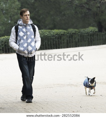 Man and dog walking in the park. Man and dog in same jacket walking in the park dark cloudy day.