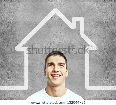 man and drawing house on wall