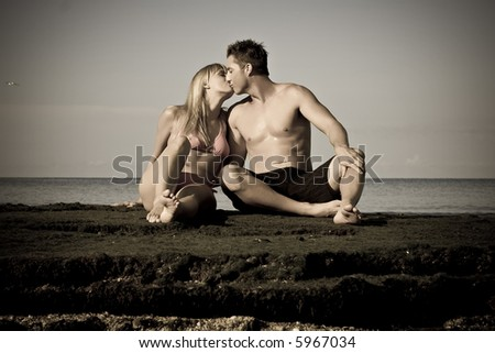 Man and female sitting at the beach on rocks, kissing. Aged photo