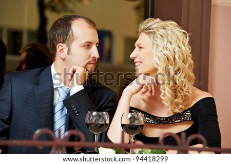 Man and girl drinking wine at street cafe on a date with flower on table