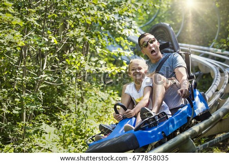 Man and girl enjoying a summer fun roller coaster ride. They have some funny expression as they enjoy a thrilling ride on a red amusement park ride