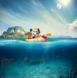 Man and girl kayaking next to a tropical island