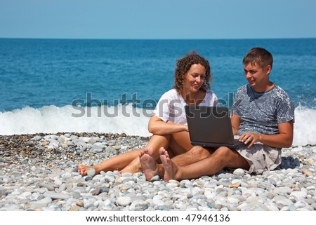 Man and girl sitting on seashore. With interest in looking at laptop standing on their knees.