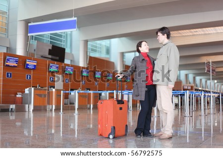 man and girl with red suitcase standing in airport hall