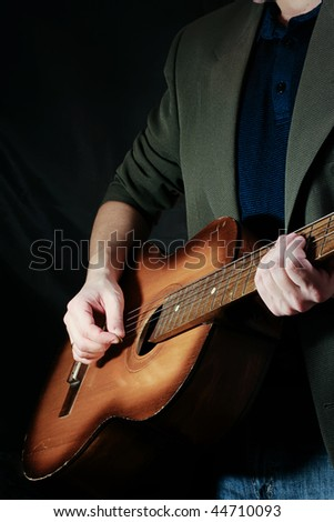man and guitar at black background