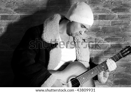 man and guitar at brick background