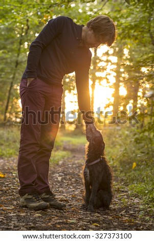 Man and his dog enjoying nature as he stands bending down to pet it in a glade in the woods backlit by the warm glow of the early morning sun.