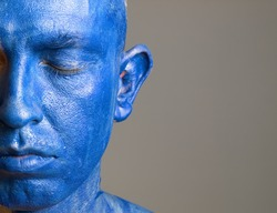Man and his face painted with color blue. The man is closed eyes and photographic composition leaves only half of the face.
