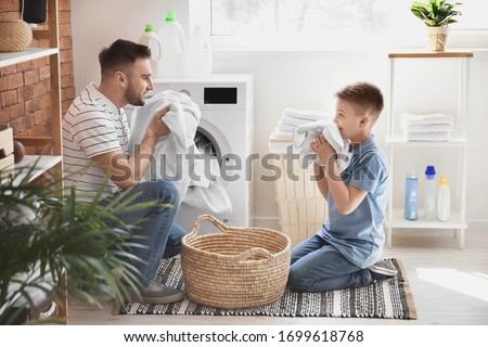 Man and his little son doing laundry at home Foto d'archivio ©