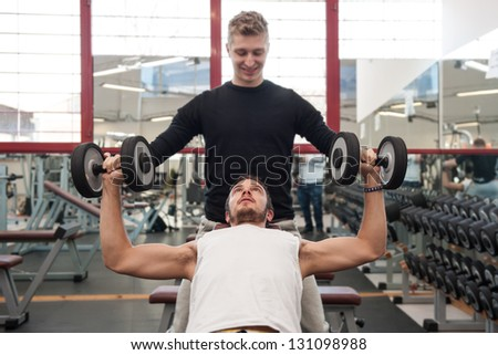 Man and his personal trainer exercising with dumbbells at the Gym. - stock photo
