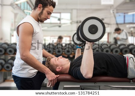 Man and his personal trainer exercising with dumbbells at the Gym.