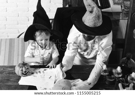 Man and kid with busy faces in witch hats draw and decorate pumpkins. Halloween and holiday concept. Man and boy in room on white brick background. Witcher and little magician get ready for Halloween. #1155005215