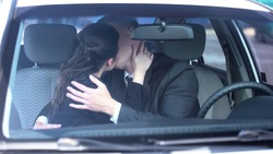 Man and lady in formal suits kissing in car, secret office affair, temptation