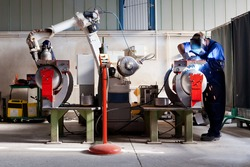 Man and robotic machine work together inside industrial building. The mechanical arm performs welds on metal components assisted by a worker who in turn manages welds manually.