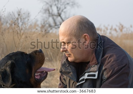 man and rottweiler dog face to face