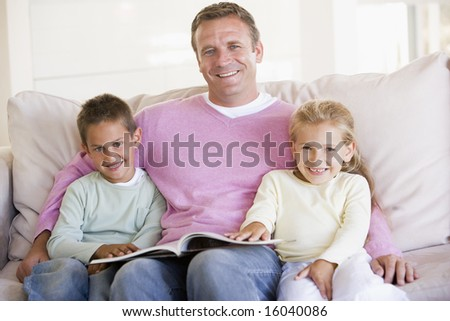 Man and two children sitting in living room reading book and smiling