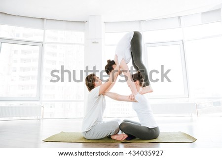 Man and two women doing stretching exercises and acro yoga in group #434035927