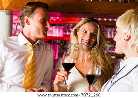 Man and two women in a hotel bar in the evening having glasses of red wine and probably a little flirt