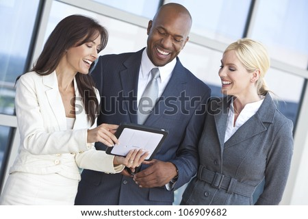 Man and two women, interracial businessman and businesswomen team using tablet computer at work