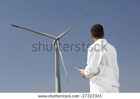 man and wind turbines; electronics engineer checking wind turbine, concept of alternative energy and ecology
