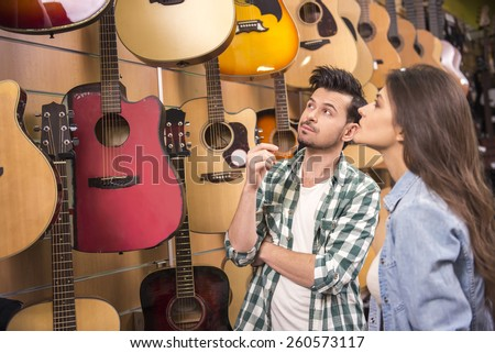 Man and woman are considering a guitars in a music store.