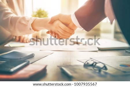 Man and woman are shaking hands in office. Collaborative teamwork.