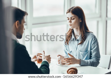 Man and woman are sitting in cafe chatting dating leisure
