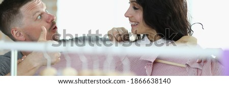 Man and woman are smiling at each other next to hanger with things. Consulting visitors in a clothing store concept Stok fotoğraf ©