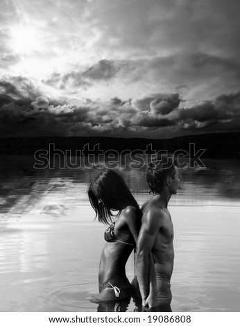 Man and woman are standing back to back in water / black and white photo