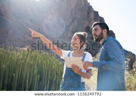 Man and woman are standing in the desert next to a mountain and the woman is pointing at the horizon