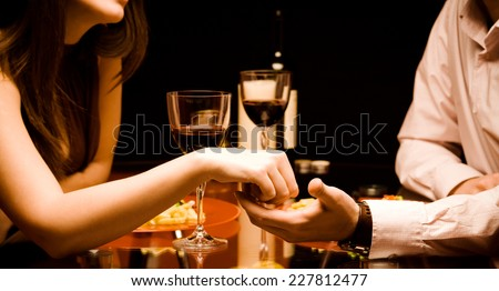 Man and woman at the restaurant - holding hands together