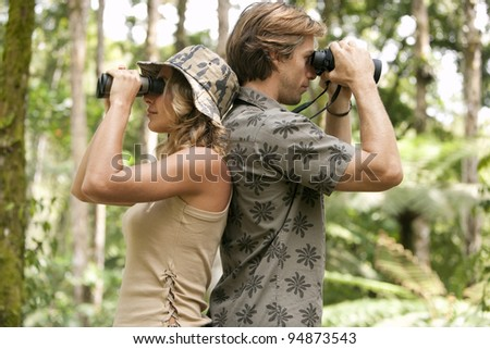 Man and woman back to back, looking through binoculars in the forest.