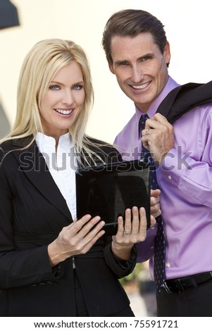 Man and woman, businessman and businesswoman team using tablet computer