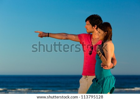 Man and woman, couple, enjoying the romantic sunset on a beach by the ocean in their vacation