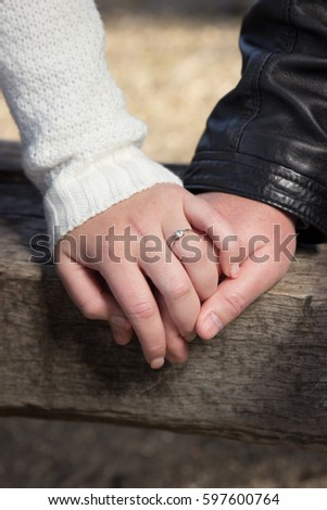 Man and woman couple holding hands on a wooden bench with engagement ring closeup #597600764