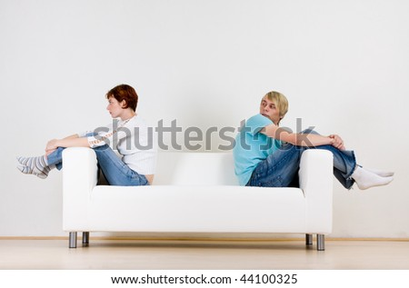 Man and woman couple sitting on opposite ends of a white couch.