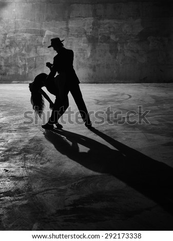 Man and woman dancing, urban dancing theme, concrete building surroundings, black and white image