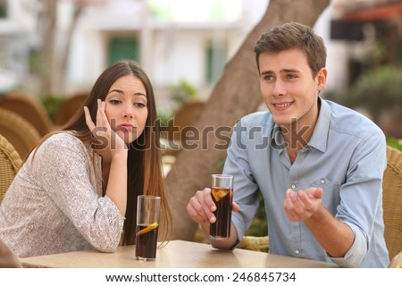 Man and woman dating in a restaurant terrace but she is boring while he telling lies