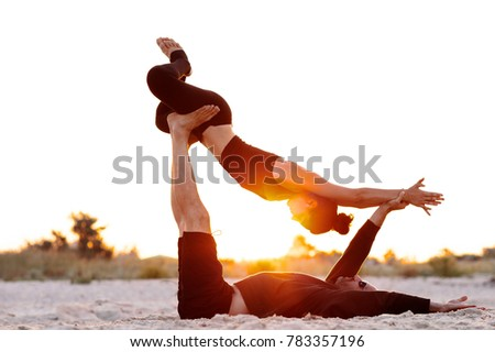man and woman doing acrobatic yoga early in the morning #783357196