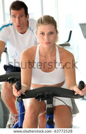 Man and woman doing indoor biking