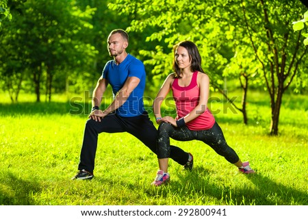 Man and woman doing stretching exercises at summer park.  Young couple exercising and stretching muscles before sport activity - outdoor in nature