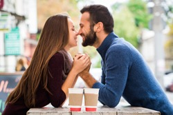 Man and woman drinking tea or coffee. Picnic. Drink warm in cool weather. Happy couple with coffee cups in autumn park. Love story concept