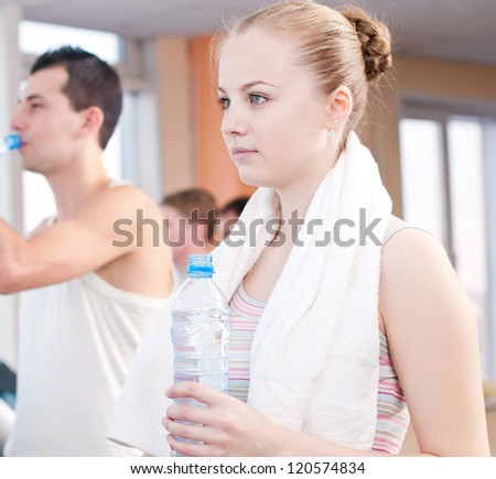 Man and woman drinking water after sports. Fitness gym.