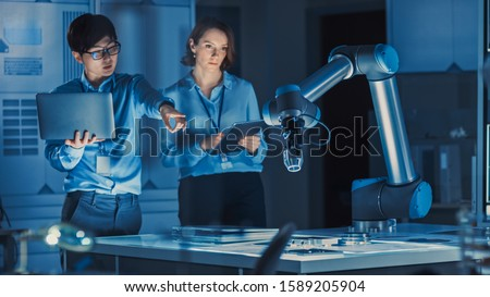 Man and Woman Engineers with Laptop and a Tablet Analyse and Discuss How a Futuristic Robotic Arm Works and Moves a Metal Object. They are in a High Tech Research Laboratory with Modern Equipment.