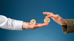 Man and woman equality in business conceptual image - female hand placing wooden cut circle with female symbol on it next to the one with male symbol.