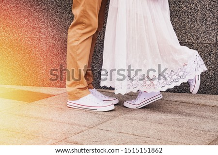 Man and woman feets close-up on urban background with sunlight effect. Bride and groom or couple on the date in same sneakers